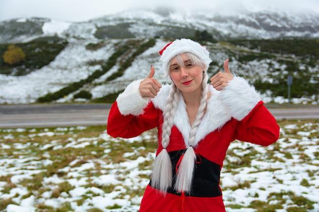 Młoda ładna kobieta w stroju świętego mikołaja na śnieżnym krajobrazie śniegu pokazuje, że jej ręce wszystko jest w porządku