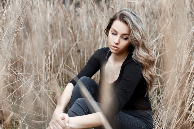 Młoda ładna kobieta w stylowych dżinsach w modnej czarnej koszulce odpoczywa siedząc na ziemi w polu