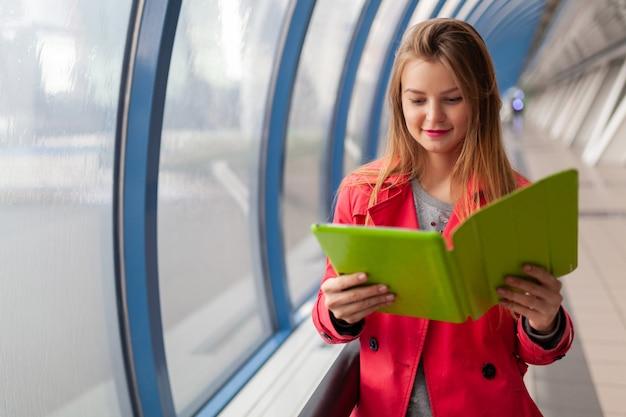 Młoda ładna kobieta w swobodnym stroju trzymając tablet laptopa w miejskim budynku, w dżinsach, różowej kurtce, w oknie z widokiem na miasto, edukacja online