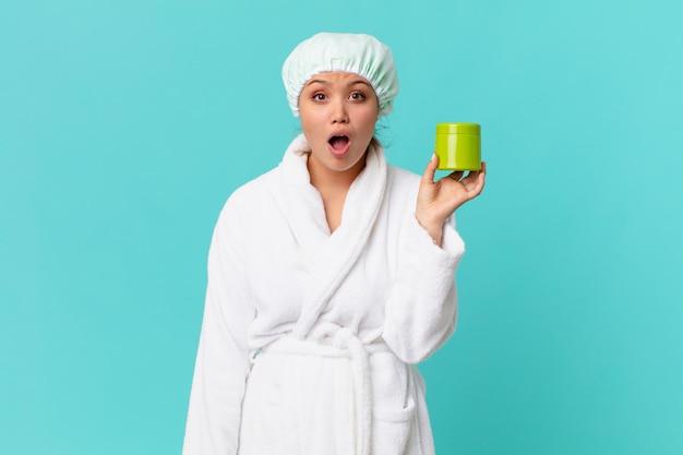 Młoda ładna kobieta w szlafroku i trzymająca czystą butelkę produktu