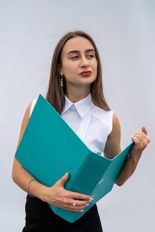 Młoda ładna kobieta w ubraniach biznesowych z folderu papieru, na białym tle. pojęcie pracy