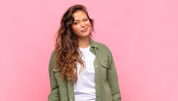 Młoda ładna kobieta w zielonej dżinsowej otwartej koszuli pozuje na różowej ścianie
