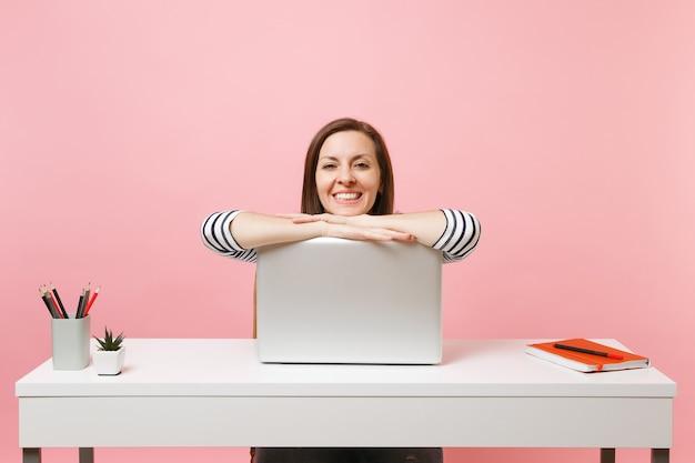 Młoda ładna kobieta w zwykłych ubraniach pracuje nad projektem, opierając się na laptopie, siedząc w biurze