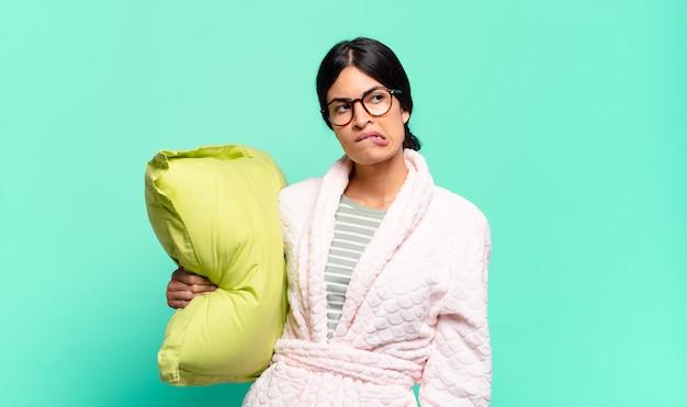 Młoda ładna kobieta wątpi lub myśli, przygryza wargę i czuje się niepewnie i nerwowo, chcąc skopiować przestrzeń z boku. koncepcja piżamy