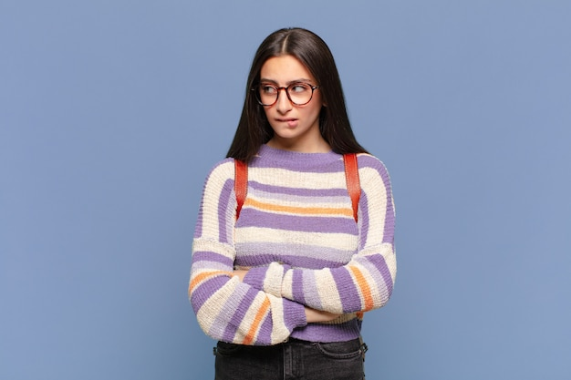 Młoda ładna kobieta wątpi lub myśli, przygryza wargę i czuje się niepewnie i zdenerwowana, chcąc skopiować przestrzeń z boku