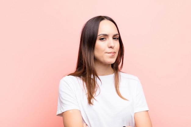 Młoda ładna kobieta wątpiąca lub myśląca, przygryzająca wargę i czująca się niepewnie i nerwowo, chcąca skopiować przestrzeń z boku na różowej ścianie