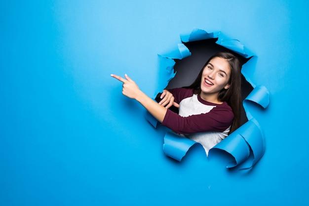 Młoda ładna kobieta wskazała stronę patrząc przez niebieską dziurę w ścianie papieru.