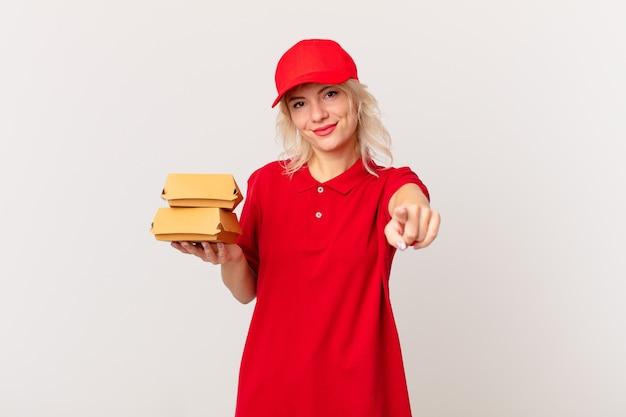 Młoda ładna kobieta, wskazując na aparat wybierając ciebie. koncepcja dostarczania burgerów