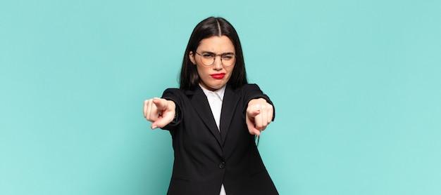 Młoda ładna kobieta, wskazując na aparat z obu palców i zły wyraz, mówiąc ci, abyś wypełnił swój obowiązek. pomysł na biznes