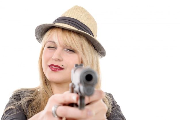 Młoda ładna kobieta wskazująca jedną ręką broń w kamerę,