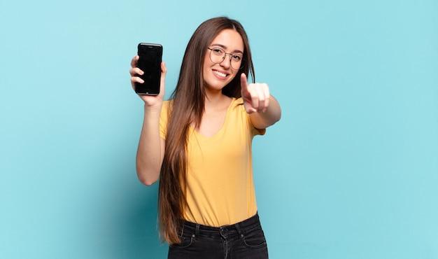 Młoda ładna kobieta wskazująca na aparat z zadowolonym, pewnym siebie, przyjaznym uśmiechem, wybierająca ciebie