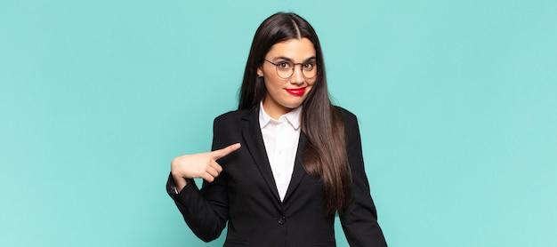 Młoda ładna kobieta wygląda dumnie, pewnie i szczęśliwie, uśmiecha się i wskazuje na siebie lub robi znak numer jeden. pomysł na biznes
