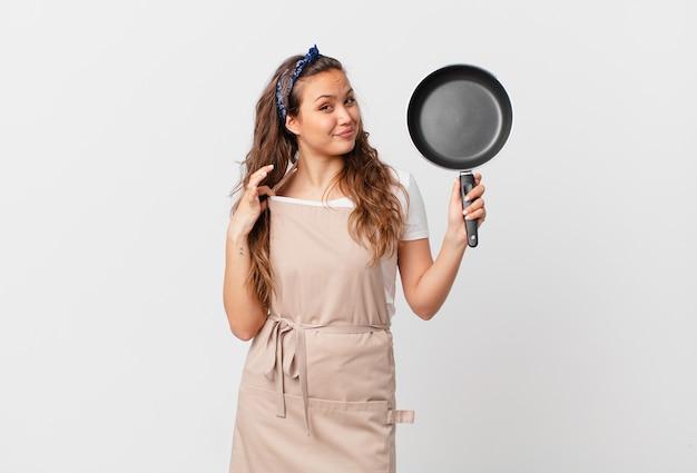Młoda ładna kobieta wygląda na arogancką, odnoszącą sukcesy, pozytywną i dumną koncepcję szefa kuchni i trzyma patelnię
