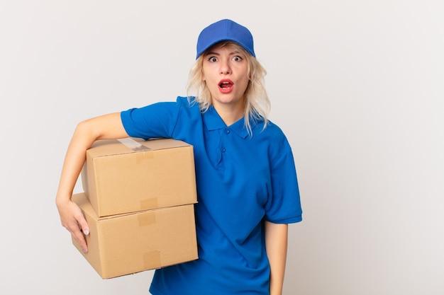 Młoda ładna kobieta wygląda na bardzo zszokowaną lub zdziwioną. koncepcja dostarczania paczek