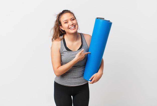 Młoda ładna kobieta wygląda na podekscytowaną i zaskoczoną, wskazując na bok i trzymając matę do jogi