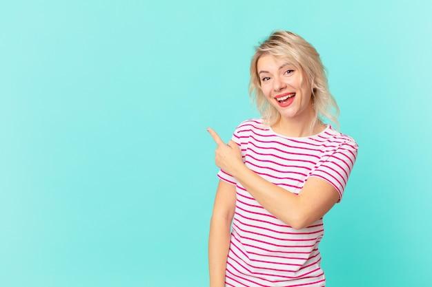 Młoda ładna kobieta wygląda na podekscytowaną i zdziwioną, wskazując na bok. kopia koncepcja przestrzeni