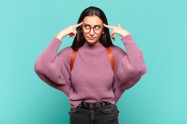 Młoda ładna kobieta wygląda na skoncentrowaną i intensywnie myśli o pomyśle, wyobrażając sobie rozwiązanie wyzwania