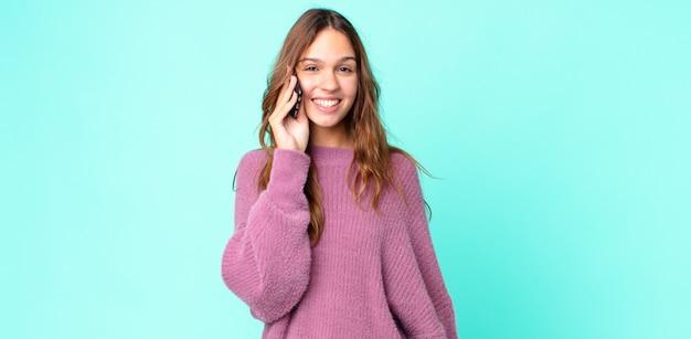Młoda ładna kobieta wygląda na szczęśliwą i mile zaskoczoną i korzysta ze smartfona