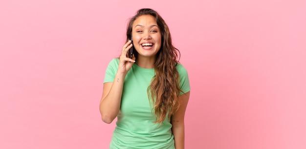 Młoda ładna kobieta wygląda na szczęśliwą i mile zaskoczoną i trzyma smartfona