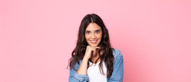 Młoda ładna kobieta wygląda na szczęśliwą i uśmiecha się z ręką na brodzie, zastanawia się lub zadaje pytanie, porównując opcje