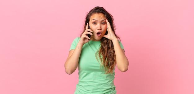 Młoda ładna kobieta wygląda na szczęśliwą, zdumioną i zaskoczoną i trzyma smartfona