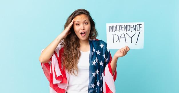 Młoda ładna kobieta wygląda na szczęśliwą, zdumioną i zaskoczoną koncepcją dnia niepodległości