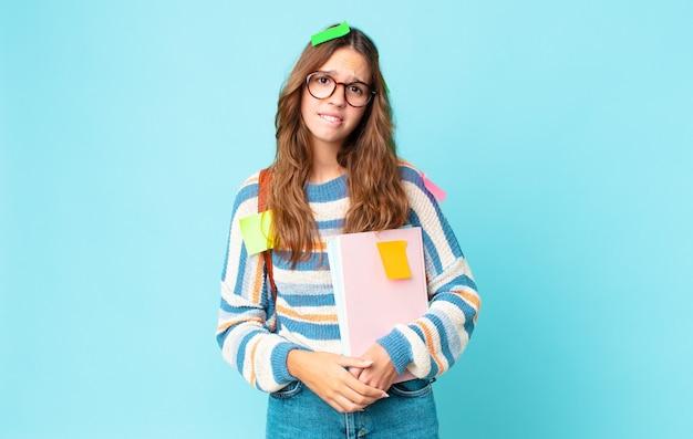 Młoda ładna kobieta wygląda na zakłopotaną i zdezorientowaną z torbą i trzymającą książki