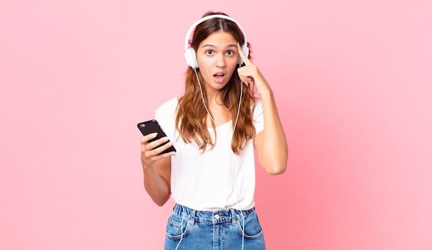 Młoda ładna kobieta wygląda na zaskoczoną, realizując nową myśl, pomysł lub koncepcję ze słuchawkami i smartfonem