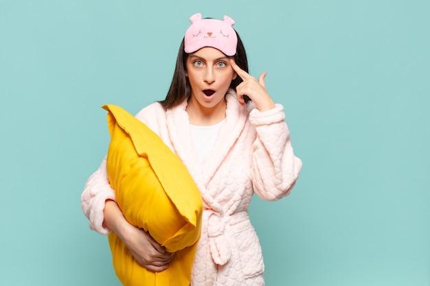 Młoda ładna kobieta wygląda na zaskoczoną, z otwartymi ustami, zszokowaną, realizującą nową myśl, pomysł lub koncepcję. budząc koncepcję piżamy