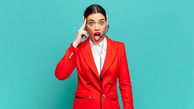 Młoda ładna kobieta wygląda na zaskoczoną, z otwartymi ustami, zszokowaną, realizującą nową myśl, pomysł lub koncepcję. koncepcja telemarketera