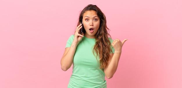 Młoda ładna kobieta wygląda na zdziwioną z niedowierzaniem i trzyma smartfona