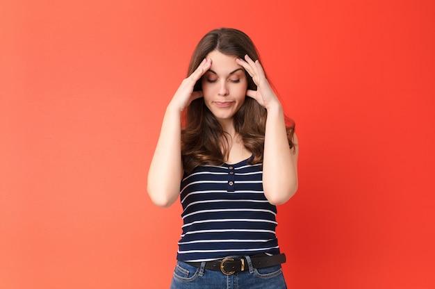 Młoda ładna kobieta wygląda na zestresowaną i sfrustrowaną, pracuje pod presją z bólem głowy i niepokoi się problemami z czerwoną ścianą