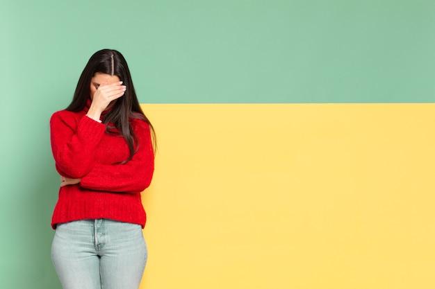 Młoda ładna kobieta wygląda na zestresowaną, zawstydzoną lub zdenerwowaną, z bólem głowy, zakrywa twarz dłonią.