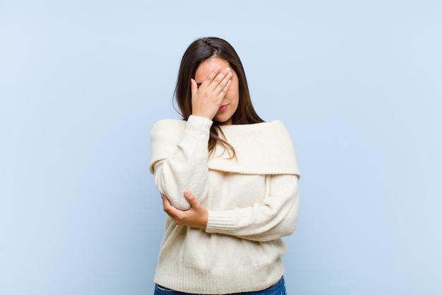 Młoda ładna kobieta wygląda na zestresowaną, zawstydzoną lub zdenerwowaną, z bólem głowy, zakrywającą twarz ręką na niebieskiej ścianie
