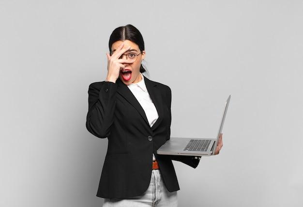 Młoda ładna Kobieta Wygląda Na Zszokowaną, Przestraszoną Lub Przerażoną, Zakrywa Twarz Dłonią I Zerka Między Palcami. Koncepcja Laptopa Premium Zdjęcia
