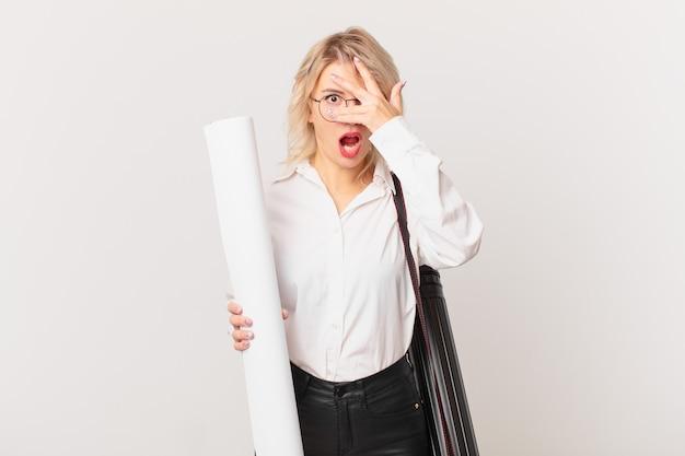 Młoda ładna kobieta wygląda na zszokowaną, przestraszoną lub przerażoną, zakrywając twarz ręką. koncepcja architekta
