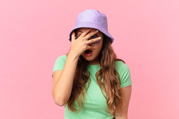 Młoda ładna kobieta wygląda na zszokowaną, przestraszoną lub przerażoną, zakrywając twarz ręką. koncepcja lato