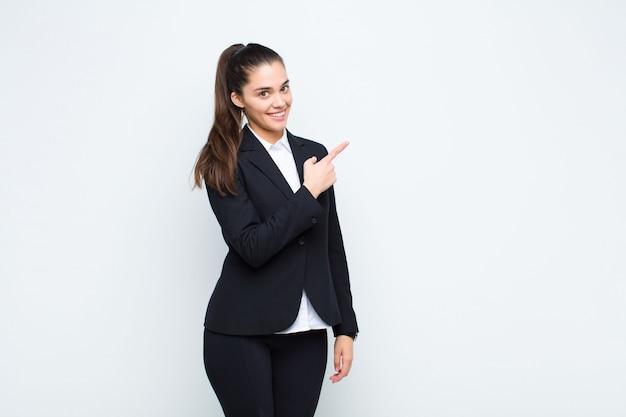 Młoda ładna kobieta wygląda podekscytowany i zaskoczony, wskazując na bok i do góry, aby skopiować koncepcję biznesową przestrzeni