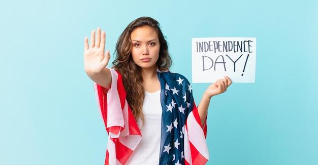 Młoda ładna kobieta wygląda poważnie pokazując otwartą dłoń, co gest zatrzymania koncepcja dnia niepodległości