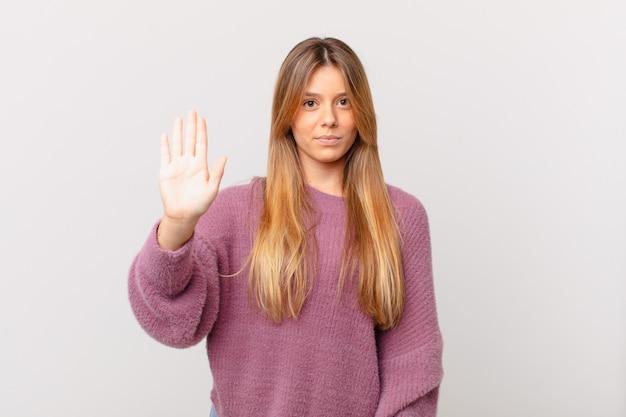 Młoda ładna kobieta wygląda poważnie pokazując otwartą dłoń, robiąc gest zatrzymania