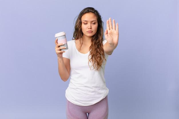 Młoda ładna kobieta wygląda poważnie pokazując otwartą dłoń, wykonując gest zatrzymania i trzymając kawę