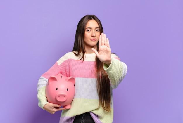 Młoda ładna kobieta wygląda poważnie, surowo, niezadowolona i wściekła, pokazując otwartą dłoń wykonującą gest stop
