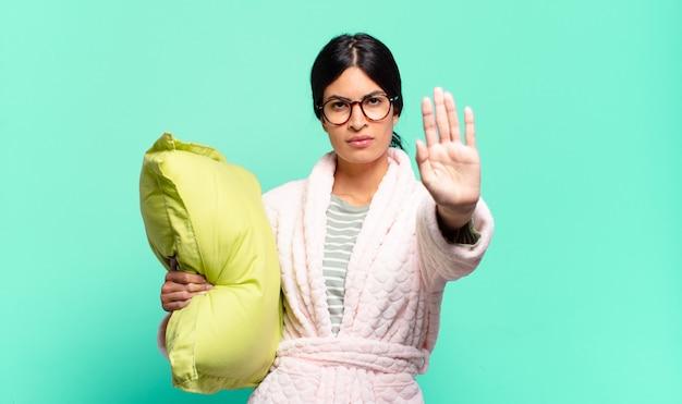 Młoda ładna kobieta wygląda poważnie, surowo, niezadowolona i zła, pokazując otwartą dłoń, robiąc gest zatrzymania. koncepcja piżamy