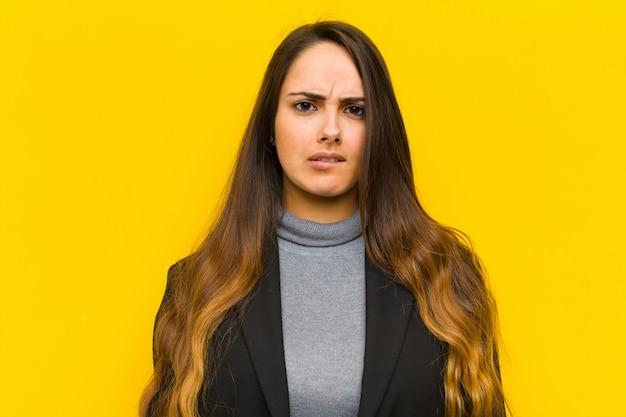 Młoda ładna kobieta wygląda zdziwiona i zdezorientowana, przygryzając wargę nerwowym gestem, nie znając odpowiedzi na problematyczną pracę lub koncepcję biznesową