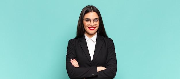 Młoda ładna kobieta wyglądająca jak szczęśliwa, dumna i usatysfakcjonowana osoba, która uśmiecha się ze skrzyżowanymi rękoma. pomysł na biznes