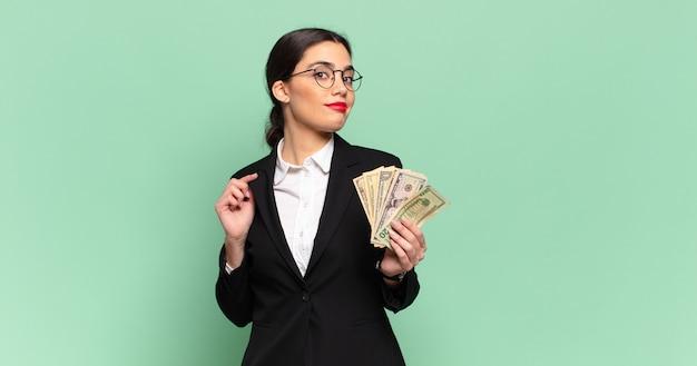 Młoda ładna kobieta wyglądająca na arogancką, odnoszącą sukcesy, pozytywną i dumną, wskazującą na siebie. koncepcja biznesu i banknotów