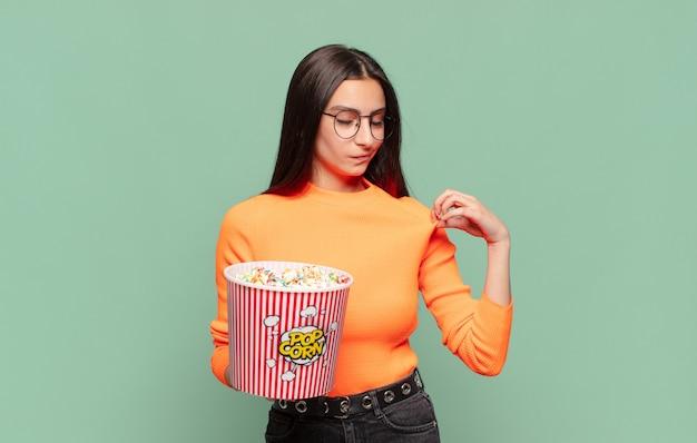 Młoda ładna kobieta wyglądająca na arogancką, odnoszącą sukcesy, pozytywną i dumną, wskazującą na siebie. koncepcja pop corns