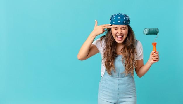 Młoda ładna kobieta wyglądająca na nieszczęśliwą i zestresowaną, gest samobójczy, który robi znak pistoletu i maluje ścianę