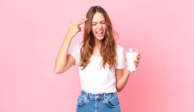 Młoda ładna kobieta wyglądająca na nieszczęśliwą i zestresowaną, samobójczy gest wykonujący znak pistoletu i trzymający szklankę mleka