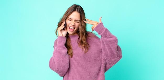 Młoda ładna kobieta wyglądająca na niezadowoloną i zestresowaną, gest samobójczy robiący znak pistoletu i używający smartfona